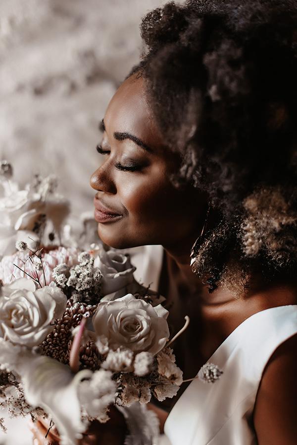 une femme en robe de mariée avec un bouquet de fleur